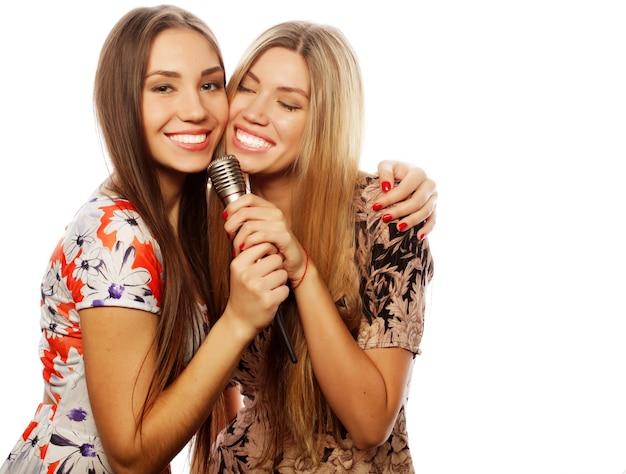 Stile di vita, felicità, concetto emotivo e di persone: due giovani ragazze che cantano, su sfondo bianco