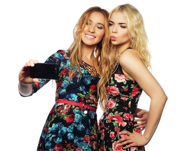 Stile di vita, felicità, emozioni e concetto di persone: due giovani donne che si fanno selfie con il cellulare