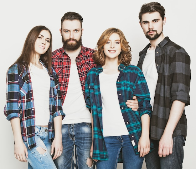 Stile di vita, felicità e concetto di persone: gruppo attraente di giovani uomini e donne felici. stile hipster. studio girato su sfondo bianco. tonificante speciale alla moda.