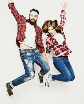 Stile di vita, felicità e concetto di persone: felice coppia di innamorati. saltando su sfondo grigio chiaro. tonificante speciale alla moda.