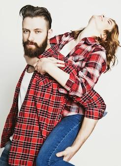 Stile di vita, felicità e concetto di persone: felice coppia di innamorati. giovane che trasporta sulle spalle la sua ragazza. studio girato su sfondo bianco. foto tonificanti speciali alla moda.