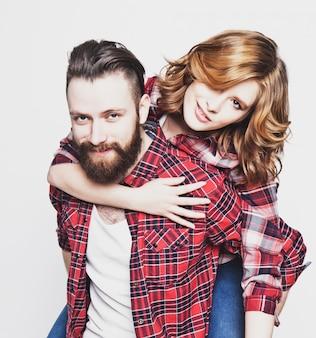 Stile di vita, felicità e concetto di persone: coppia di innamorati felici. giovane che trasporta sulle spalle la sua ragazza. sopra lo spazio bianco foto tonificanti alla moda speciali.