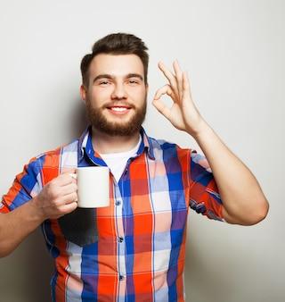Stile di vita, felicità e concetto di persone: giovane uomo barbuto con una tazza di caffè in mano e mostrando okey, su sfondo grigio.