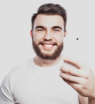Stile di vita, felicità e concetto di persone: giovane uomo barbuto con telefono cellulare in mano su sfondo grigio.