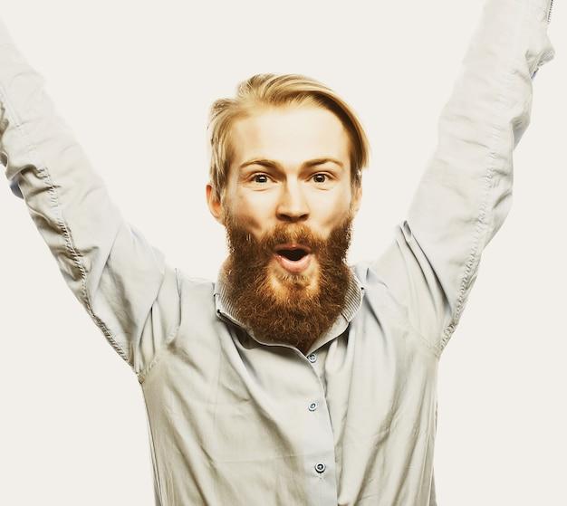 Stile di vita, felicità e concetto di persone: giovane uomo barbuto di positività che mostra la mano in piedi su sfondo grigio.