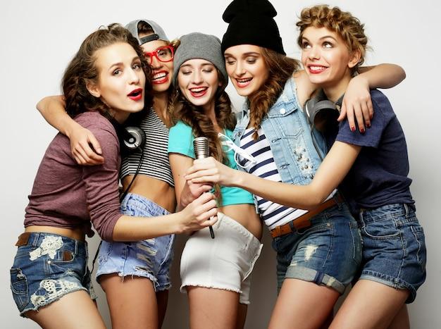 Stile di vita e concetto di persone: belle ragazze alla moda hipster che cantano al karaoke