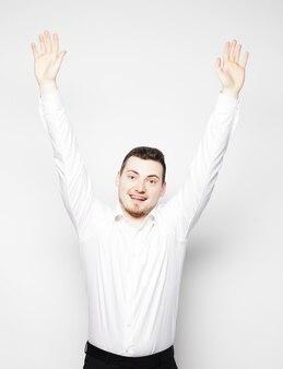 Stile di vita e concetto di persone: giovane casual in camicia con entrambe le mani sollevate in aria. vincitore e felice.