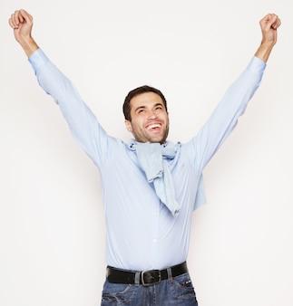 Stile di vita e concetto di persone: giovane casual in camicia con entrambe le mani alzate in aria. vincitore e felice.