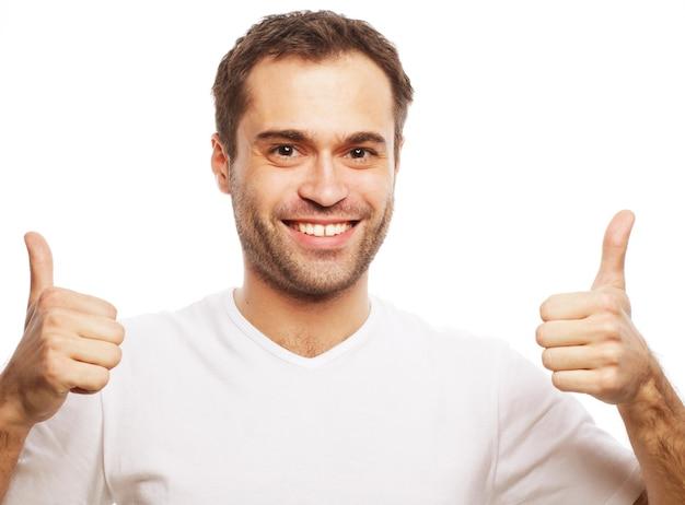 Stile di vita e concetto di persone: uomo bello felice che indossa una maglietta bianca che mostra i pollici su sfondo isolato