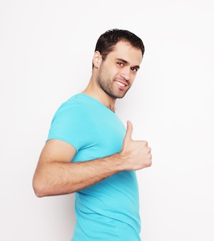Stile di vita e concetto della gente: giovane felice in camicia blu che mostra i pollici in su. su sfondo bianco.