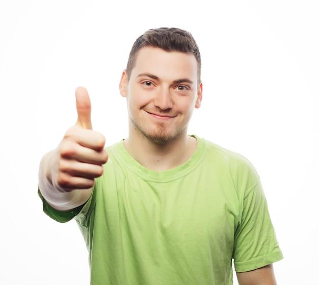Stile di vita e concetto di persone. felice giovane uomo in camicia verde che mostra i pollici in su isolato su bianco.