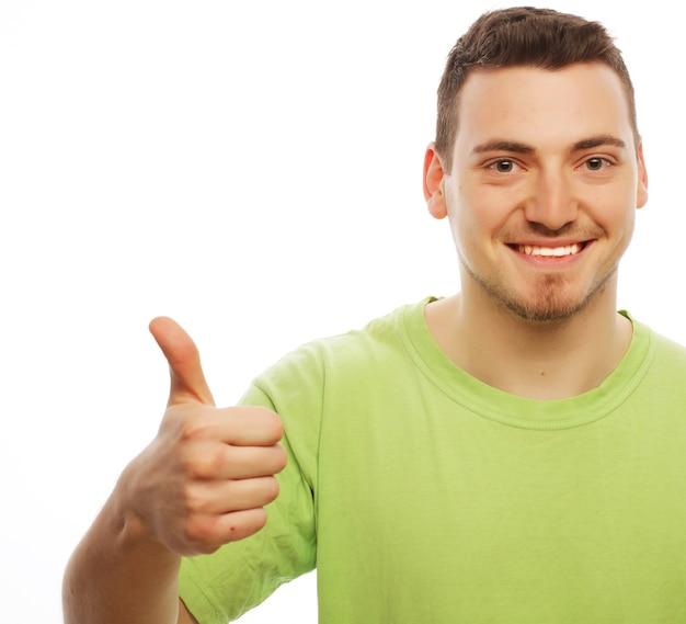 Stile di vita e concetto della gente: giovane felice in camicia verde che mostra i pollici in su. isolato su bianco.