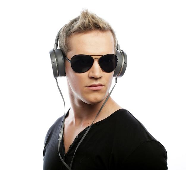 Stile di vita e concetto di persone: felice giovane che ascolta musica con le cuffie