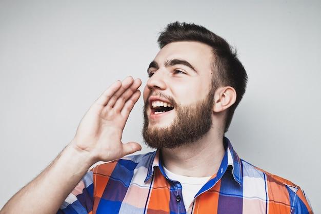 Stile di vita e concetto di persone: ritratto di un bel giovane che urla, su uno sfondo grigio