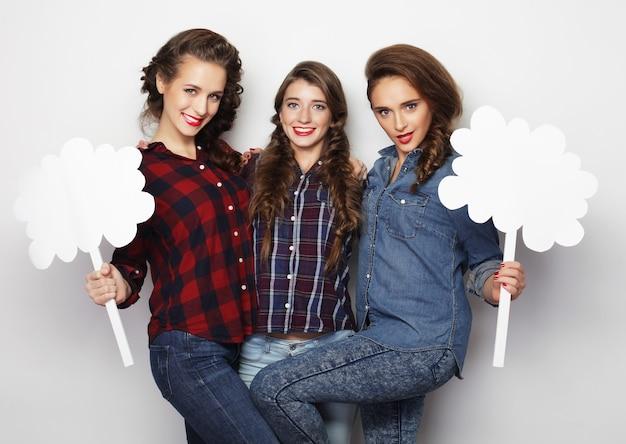 Stile di vita e concetto di persone: ragazze alla moda migliori amici che tengono carta bianca sul bastone.