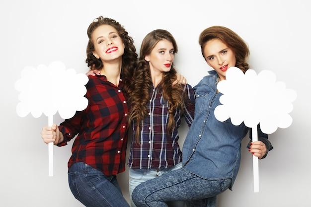 Stile di vita e concetto di persone: ragazze alla moda migliori amiche che tengono carta bianca sul bastone.