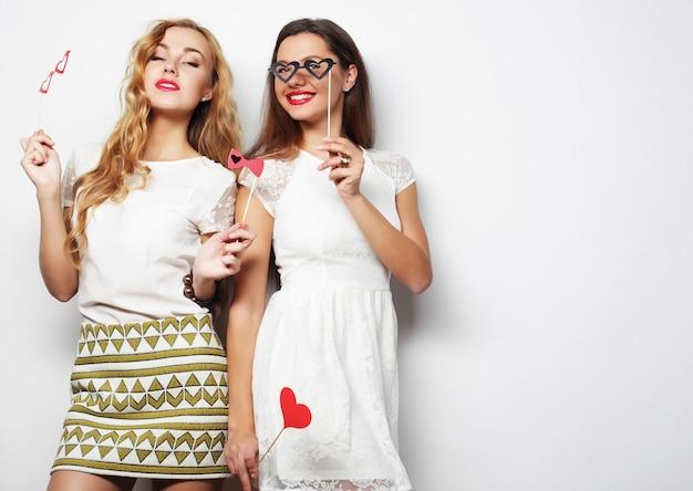 Stile di vita e concetto di persone: due eleganti migliori amiche di ragazze sexy pronte per la festa, su sfondo bianco