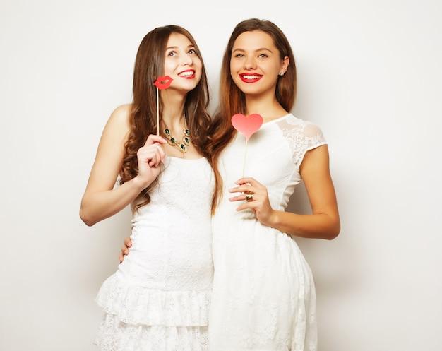 Stile di vita e concetto di persone: due eleganti migliori amiche di ragazze sexy pronte per la festa, su una superficie bianca white
