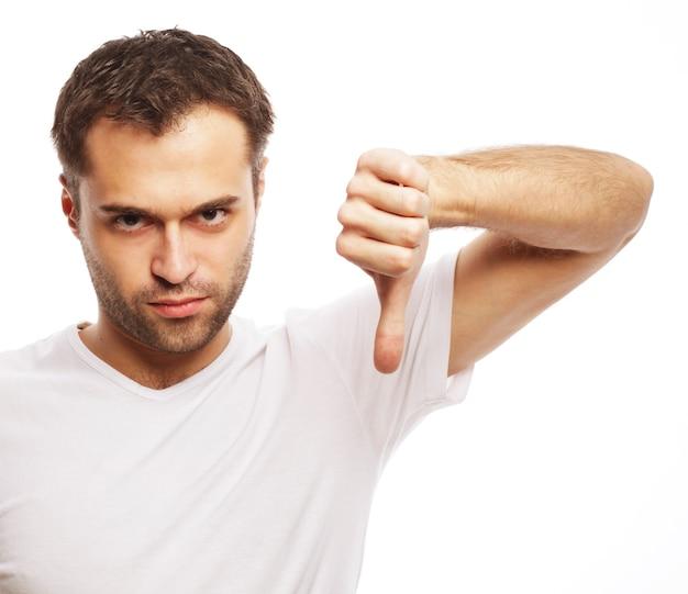 Stile di vita e concetto di persone: giovane uomo casual che fa il pollice verso il segno negativo della mano su sfondo bianco
