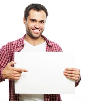 Stile di vita e concetto di persone: giovane uomo bello che mostra un cartello bianco, isolato su sfondo bianco