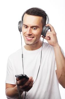 Stile di vita e concetto di persone: giovane che si gode la musica con le cuffie, ascolta musica su sfondo bianco e sorride. tempo felice.