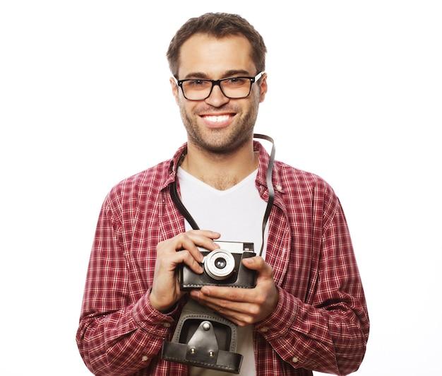 Stile di vita e concetto di persone: giovane con una fotocamera retrò su sfondo bianco