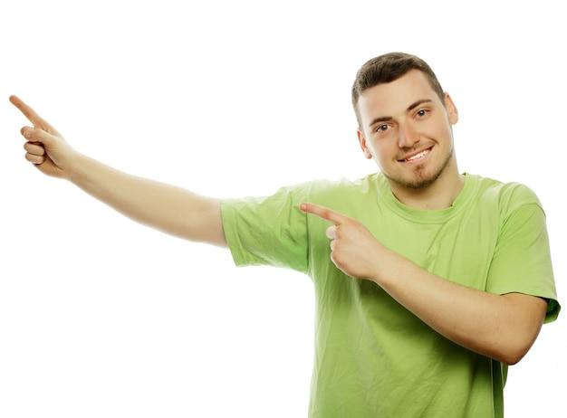 Stile di vita e concetto di persone: il giovane uomo felice sorridente mostra qualcosa su sfondo bianco.