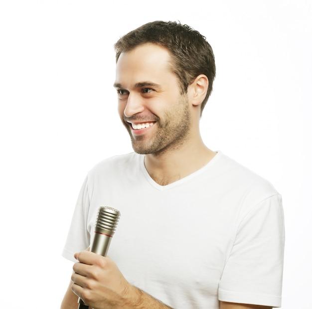 Stile di vita, persone e concetto di svago: un giovane che indossa una camicia bianca che tiene un microfono e che canta. isolato su bianco.