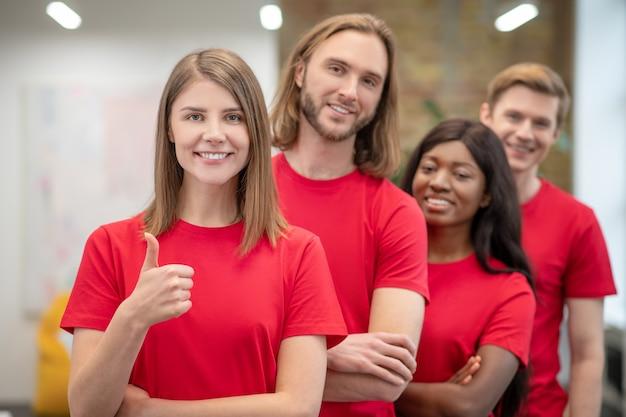 Stile di vita. ragazza graziosa sorridente che mostra gesto giusto e volontari degli amici in magliette rosse che stanno dietro