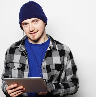 Stile di vita, tecnologia e concetto di persone: bel giovane che indossa camicia e cappello che lavora su tablet digitale e sorride mentre si trova in piedi su sfondo grigio