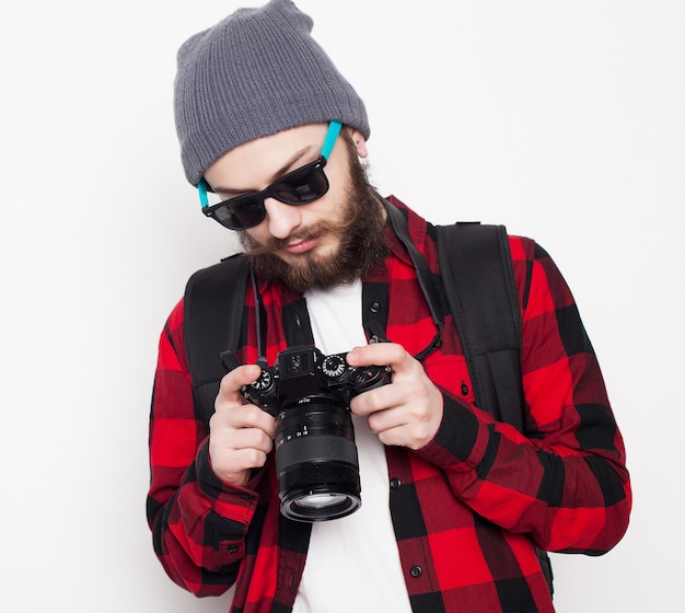 Stile di vita, tecnologia e concetto di persone: fotografo professionista. ritratto di giovane fiducioso in camicia che tiene la macchina fotografica su sfondo bianco