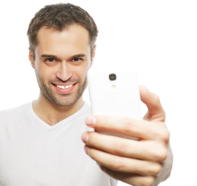 Stile di vita, tecnologia e concetto di persone: un giovane uomo in camicia che tiene in mano il telefono cellulare e fa una foto di se stesso mentre si trova in piedi su uno sfondo bianco.