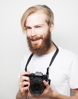 Stile di vita, tecnologia e concetto di viaggio: uomo barbuto che indossa la maglietta bianca con una fotocamera digitale isolata su uno sfondo bianco
