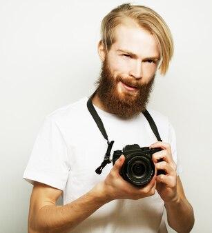 Stile di vita, tecnologia e concetto di viaggio: uomo barbuto che indossa una maglietta bianca con una fotocamera digitale isolata su uno sfondo bianco