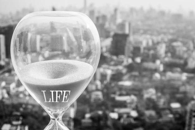 Concetto di tempo di vita con clessidra e sfondo del paesaggio urbano
