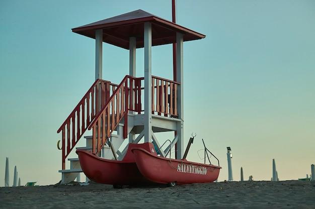Scialuppa di salvataggio e scialuppa di salvataggio in uno stabilimento balneare di rosolina mare in veneto, italia. stazione di salvataggio per bagnanti in spiaggia.