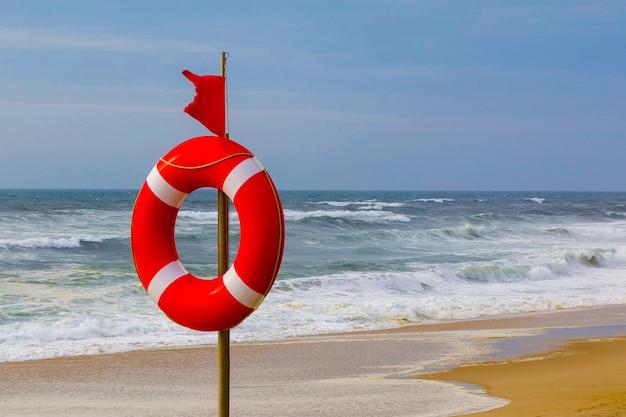 Salvagente e bandiera rossa di avvertimento che svolazzano nel vento sulla spiaggia in caso di tempesta un simbolo del deterioramento del tempo il pericolo di nuotare in un mare o in un oceano in tempesta