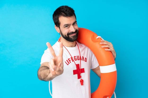 Uomo del bagnino sopra il blu che sorride e che mostra il segno di vittoria