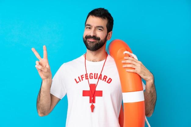 Uomo del bagnino sopra la parete blu isolata che mostra il segno di vittoria con entrambe le mani