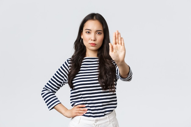 Stile di vita, bellezza e moda, concetto di emozioni delle persone. una donna asiatica dispiaciuta dall'aspetto serio dice di fermarsi, allungare la mano delusa per proibire o limitare qualcosa di brutto che accade