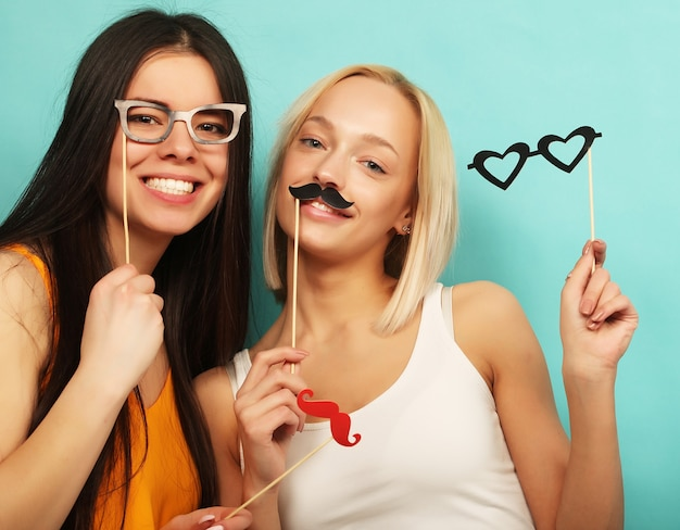 Concetto di stile di vita, bellezza e persone: i migliori amici di ragazze alla moda sexy hipster pronti per la festa. sfondo blu.