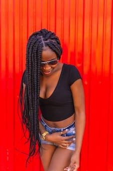 Stile di vita ragazza nera con grande treccia in pantaloncini di jeans maglietta nera e occhiali da sole su una parete rossa