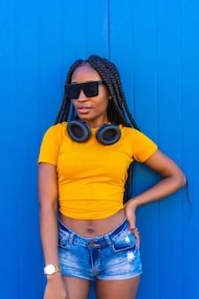 Stile di vita, ragazza nera con lunghe trecce, in una camicia gialla e occhiali da sole. dj con le cuffie sorridenti