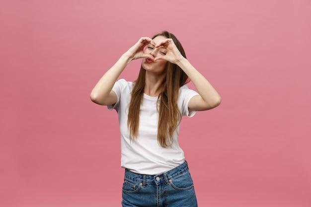 Concetto di stile di vita: bella donna attraente in camicia bianca che fa un simbolo del cuore con le sue mani