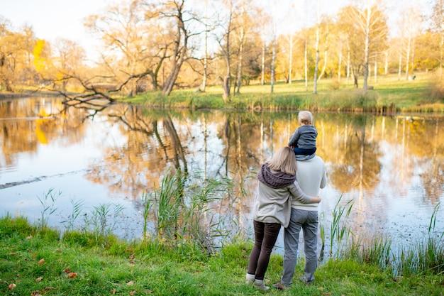 Famiglia stile di vita da dietro con il loro bambino sulle spalle dei padri in piedi sulla riva del lago