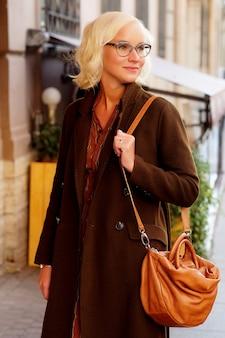 Ritratto di moda lifestyle di giovane donna alla moda che cammina per strada, indossando un vestito alla moda carino
