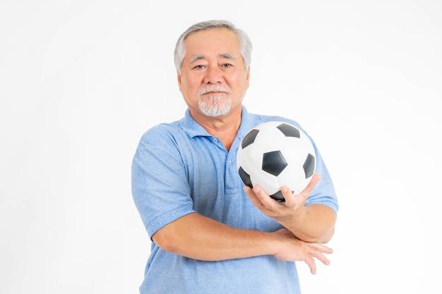 Stile di vita sano uomo anziano che tiene in mano il pallone da calcio si prepara per il preferito della squadra di allegria isolato su sfondo bianco