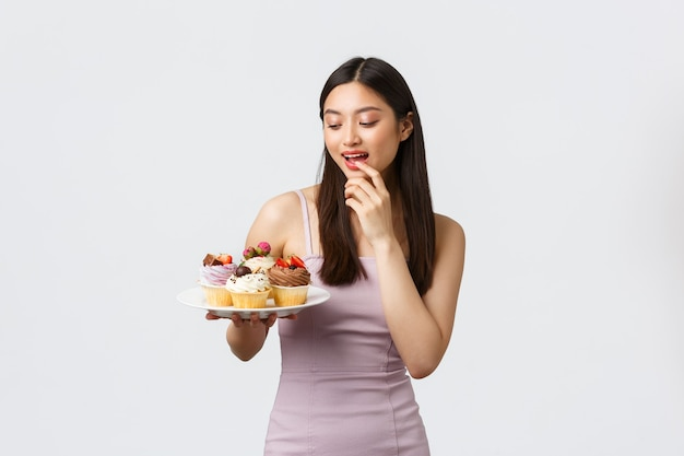 Stile di vita, vacanze, celebrazione e concetto di cibo. bella donna asiatica in vestito
