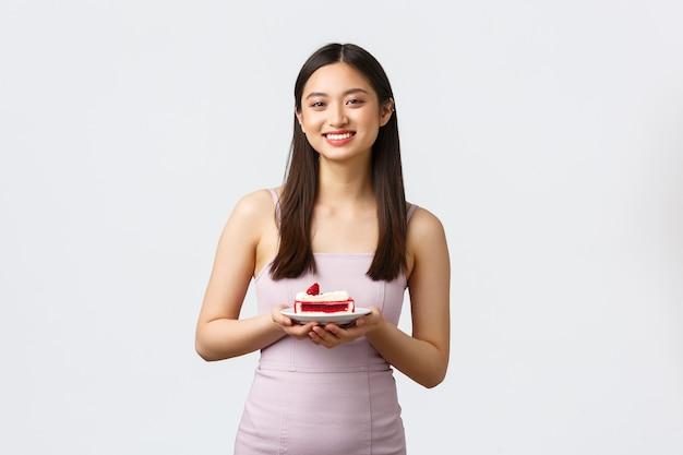 Stile di vita, vacanze, celebrazione e concetto di cibo. bella donna asiatica sorridente in abito da sera