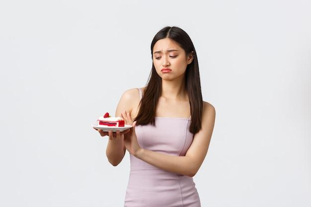 Stile di vita, vacanze, celebrazione e concetto di cibo. riluttante e sconvolta, cupa donna asiatica in abito, rifiutando di mangiare la torta